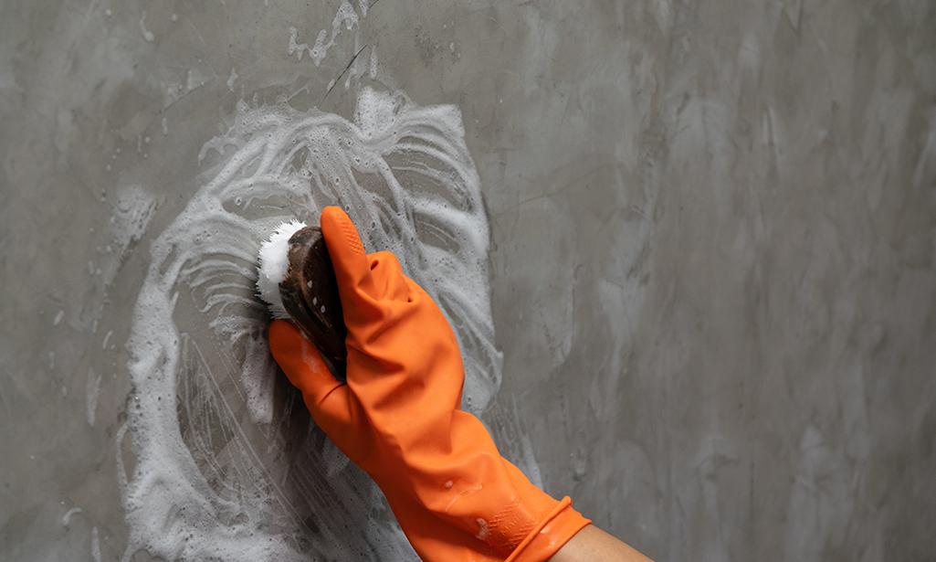 bàn tay đeo găng tay để chà giấy dán tường bằng bàn chải