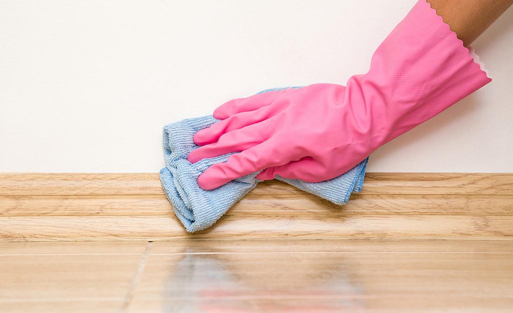 bàn tay đeo găng tay lau giấy dán tường gần chân tường