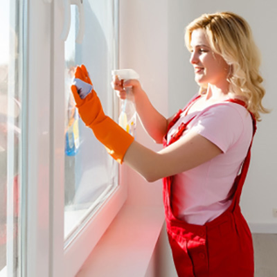 Woman in an apron cleaning a large picture window.