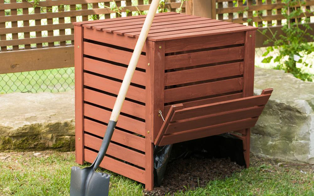 a wooden composter in a yard with a shovel leaning against it