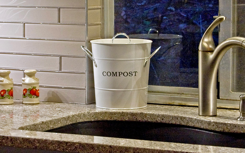 compost pail sitting on a countertop next to kitchen sink