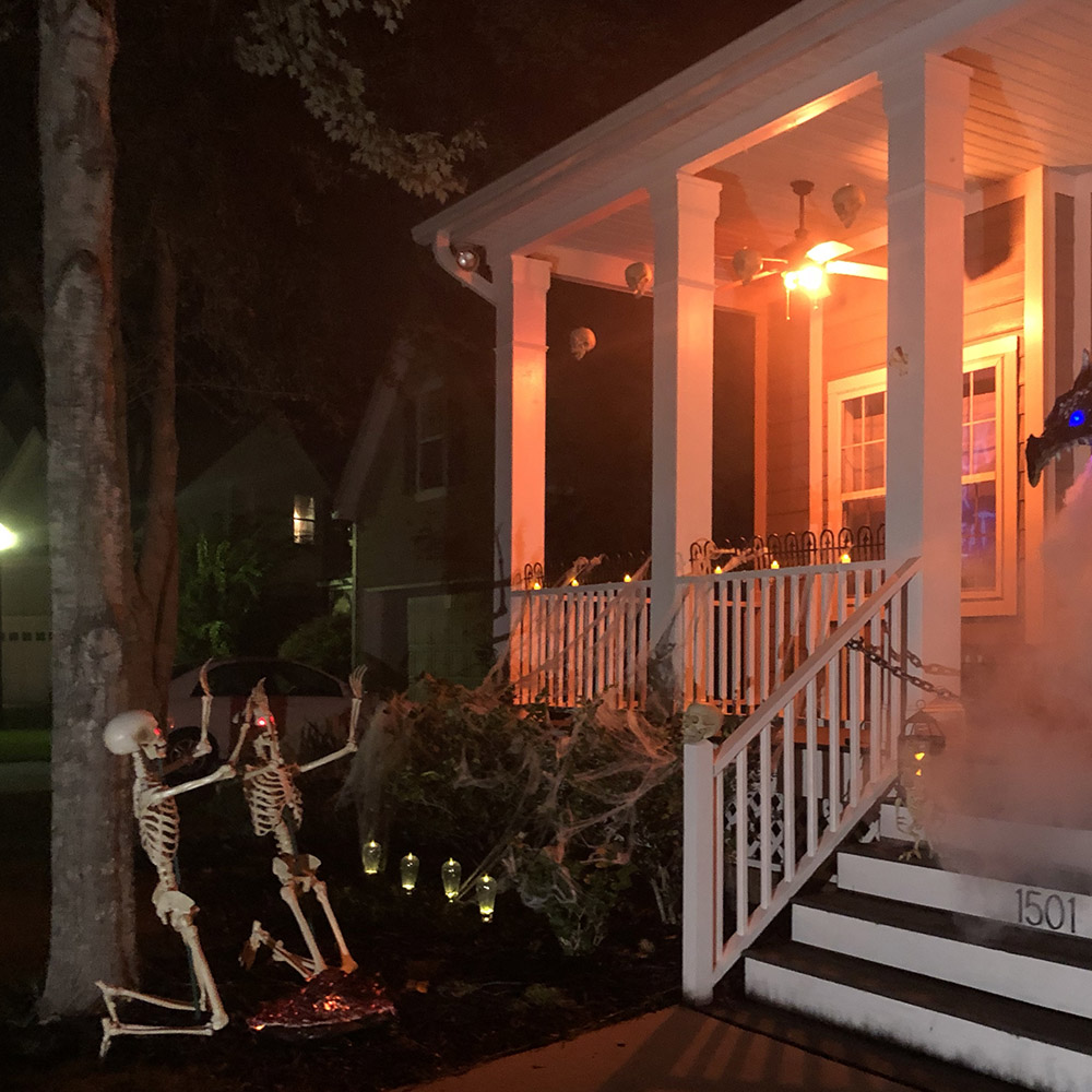 Two skeleton with glowing red eyes kneel in front of a scary Halloween porch.