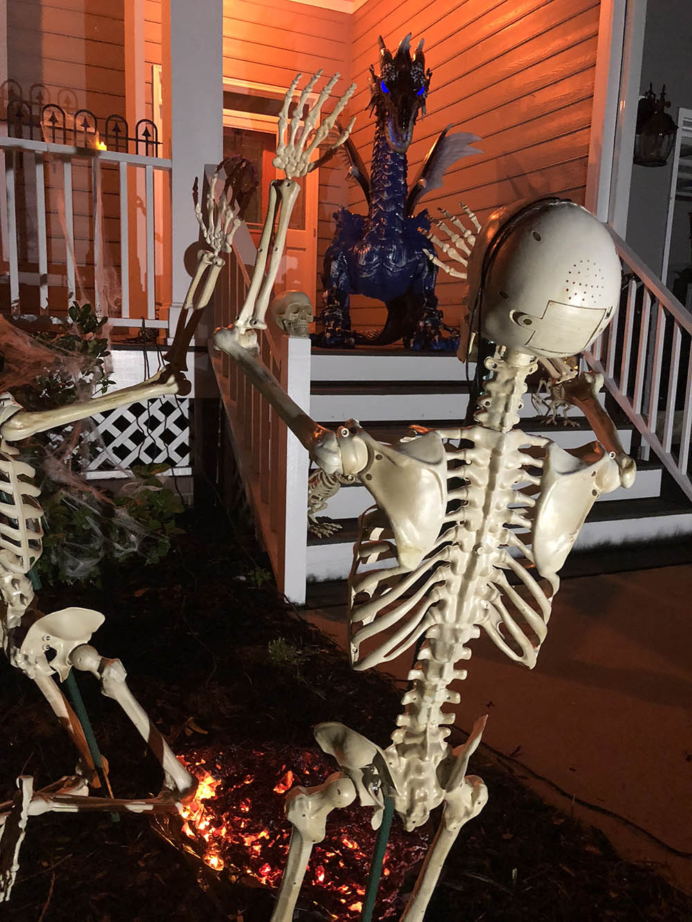 A pair of skeletons look up at a large dragon on a scary Halloween porch.