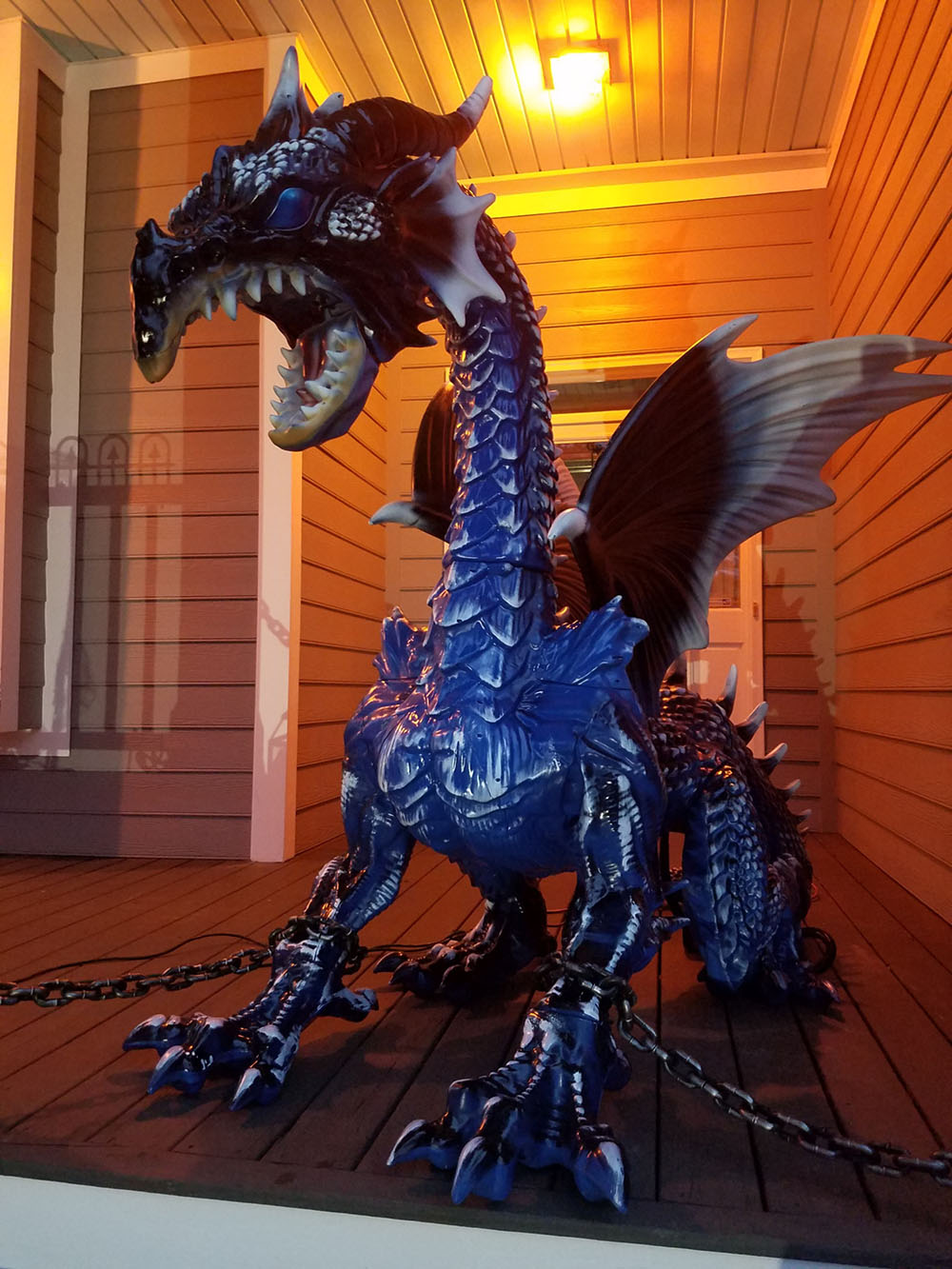 A large dragon with chains sitting on a front porch.