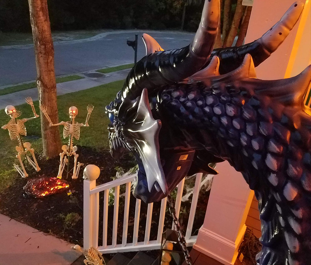 A dragon looking down at two skeletons in a yard.