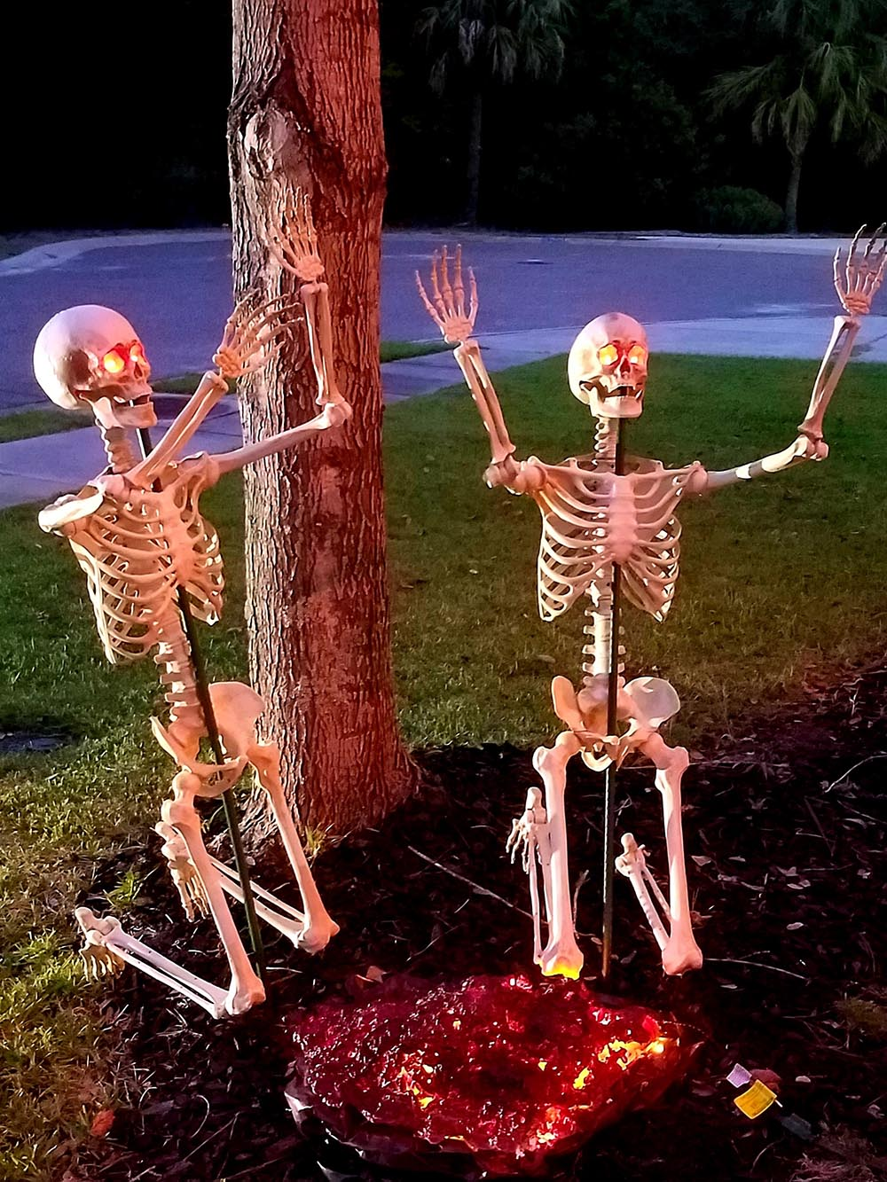 Two skeletons with glowing red eyes kneel in front of a fire.