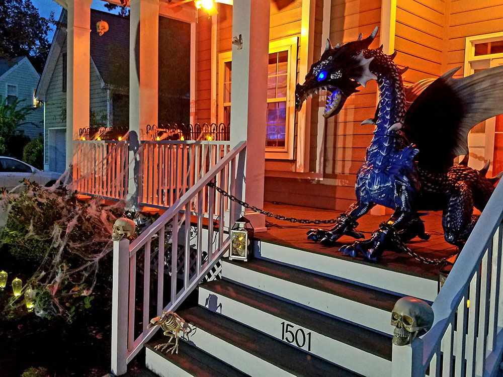 A scary Halloween porch with amber lights, skulls, and a large dragon.