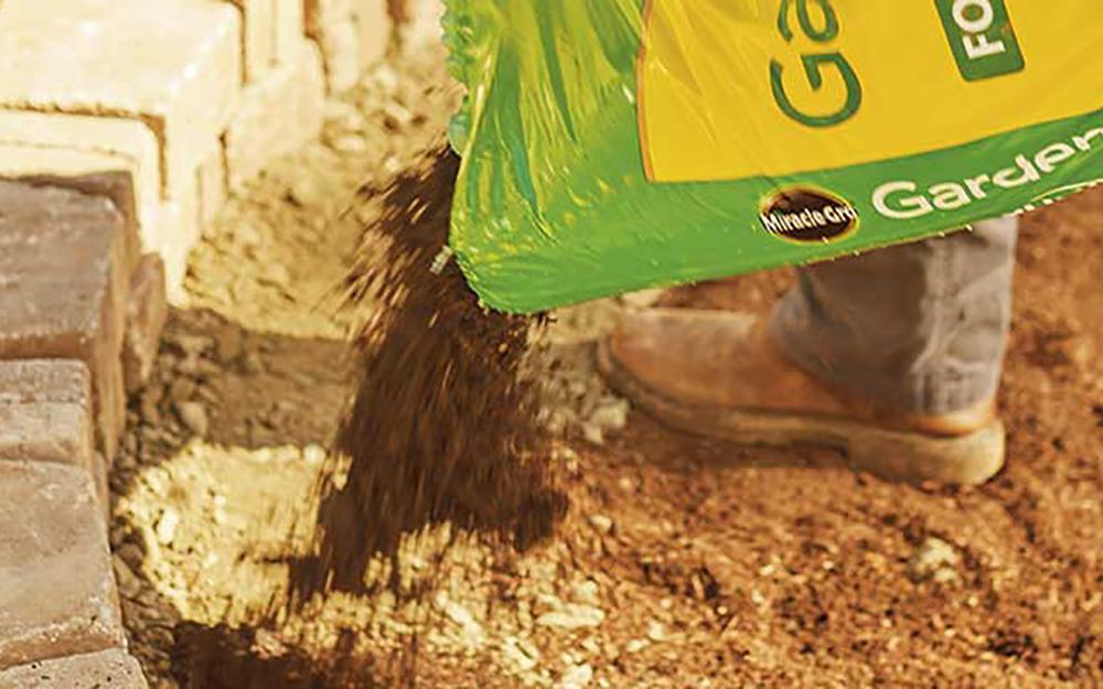 A person pouring garden soil along a paver wall.