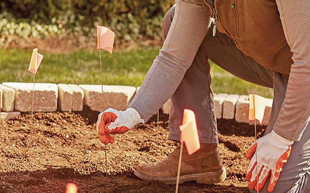 A person measuring a garden space.
