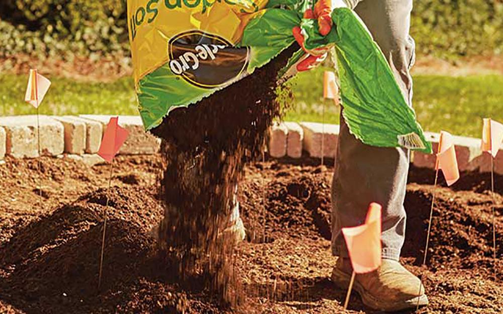 A person pouring garden soil onto a garden space.