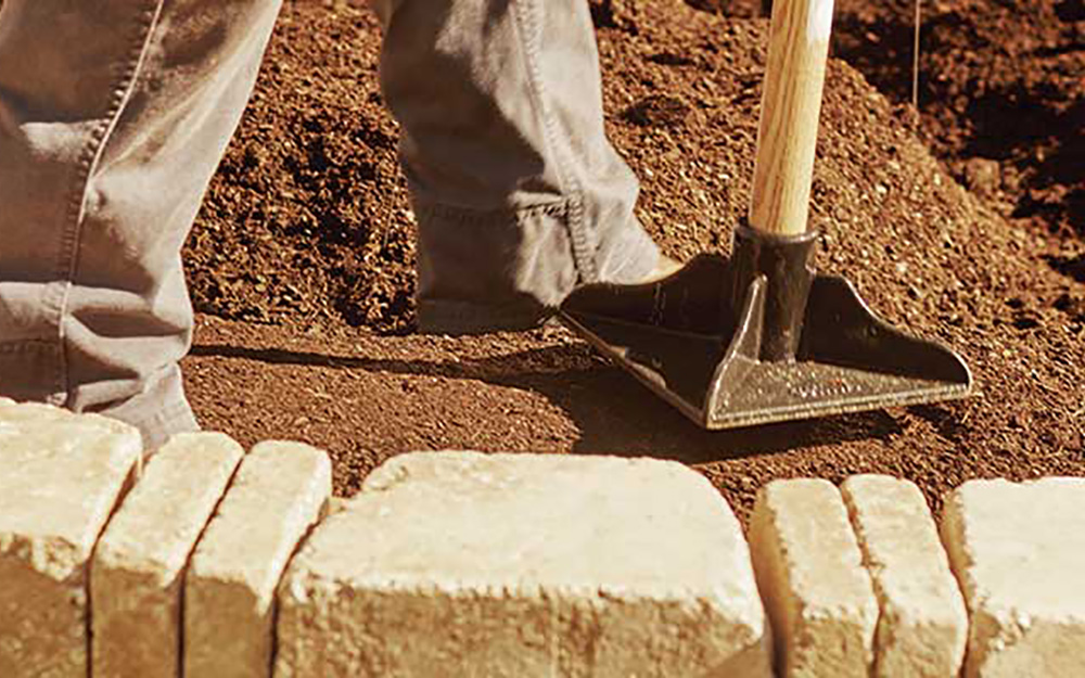 A person using a tamper to flatten soil.