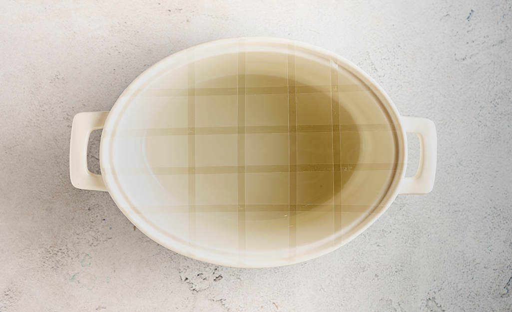 A white bowl with a taped grid on a table.