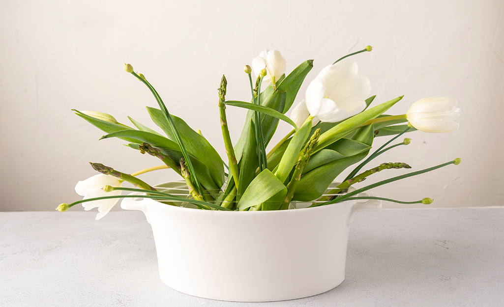 White tulips and asparagus in a white pot.