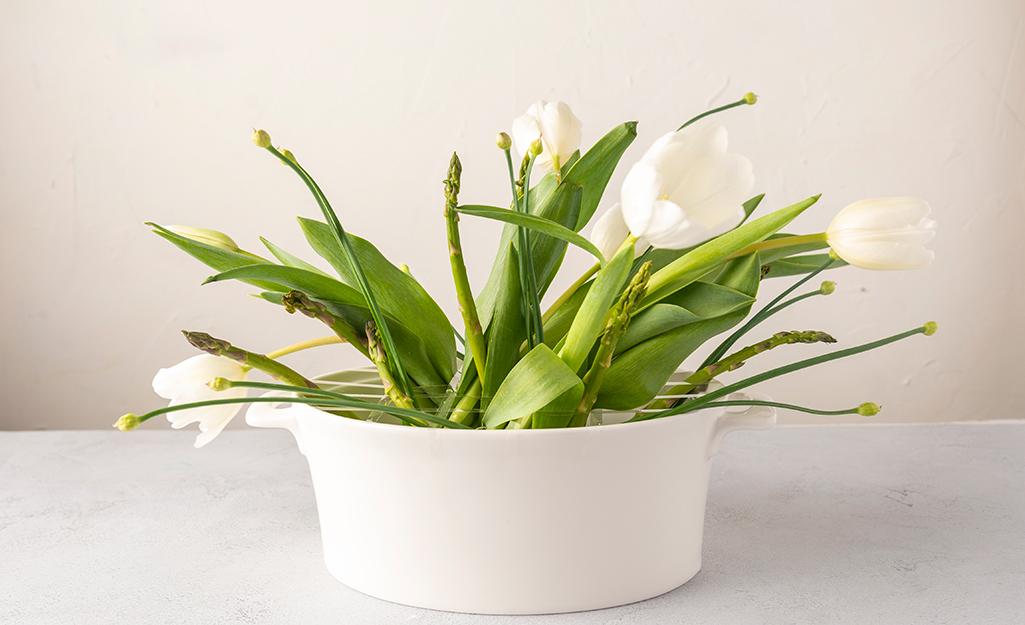 Hoa tulip trắng và măng tây trong chậu trắng.