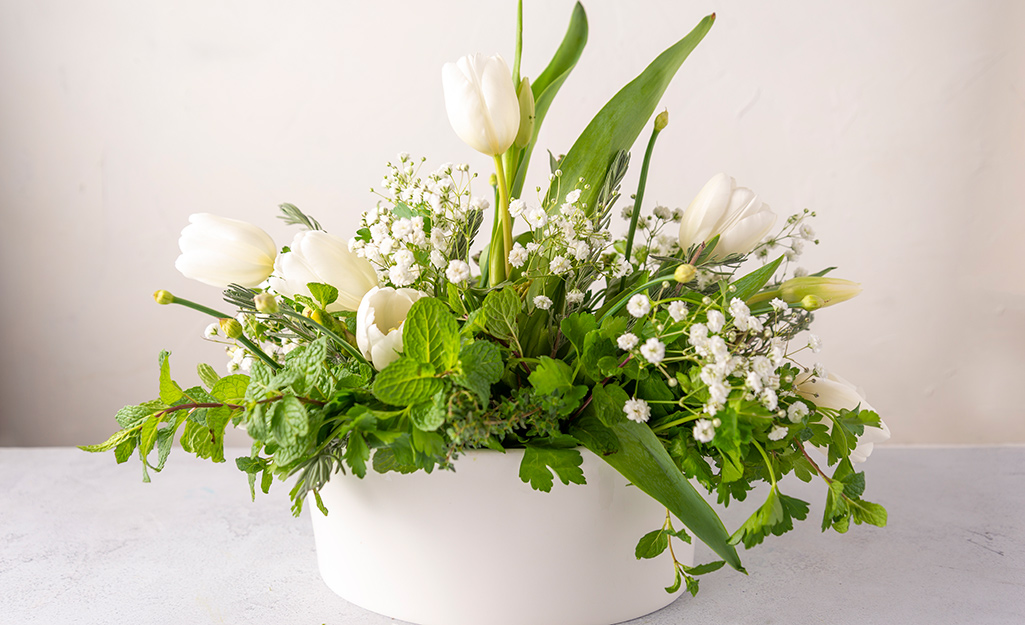 Herbs and flowers in a white pot.