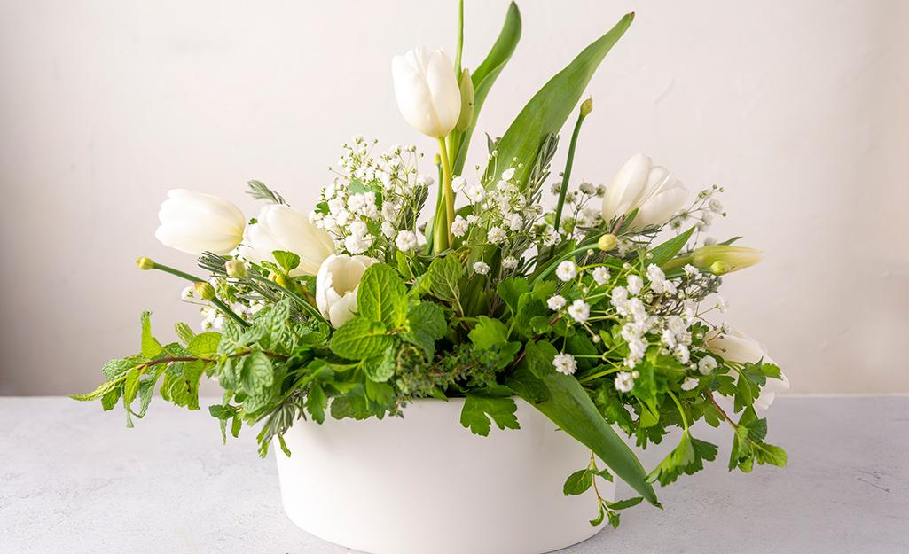 Các loại thảo mộc và hoa trong một chậu màu trắng.