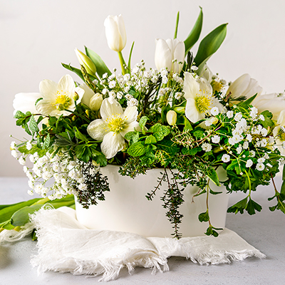 A centerpiece arrangement with foliage and white flowers.