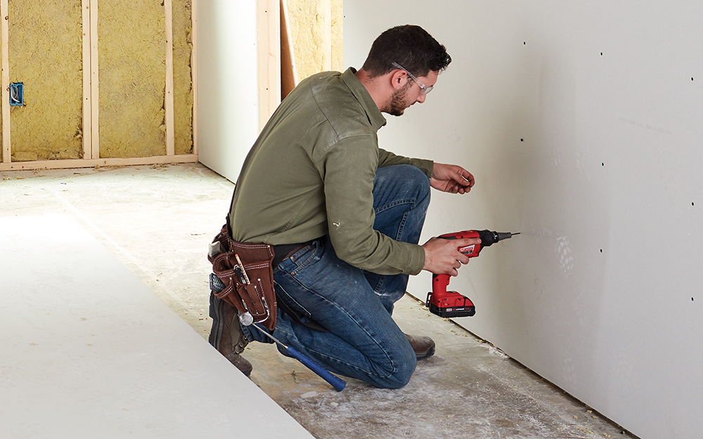 Man attaching new drywall to a wall stud with a drill.