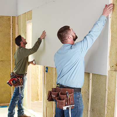 Two men installing drywall.