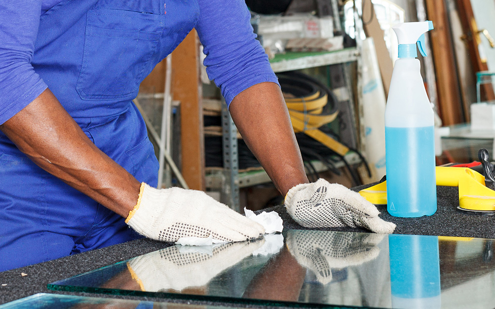 a person cleaning and lubricating a sheet of glass