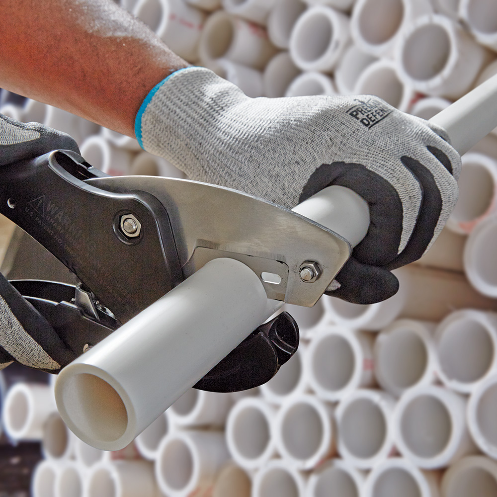 A person cuts PVC pipe with a handheld cutter.