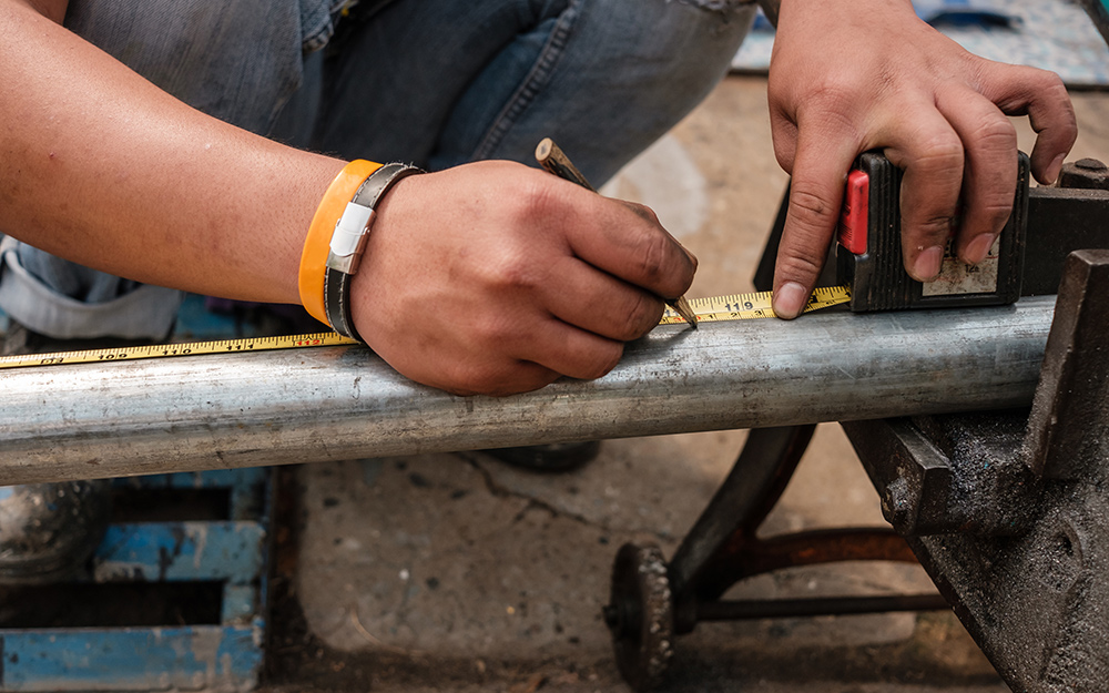 A person makes a mark on a length of steel pipe with the help of a tape measure.