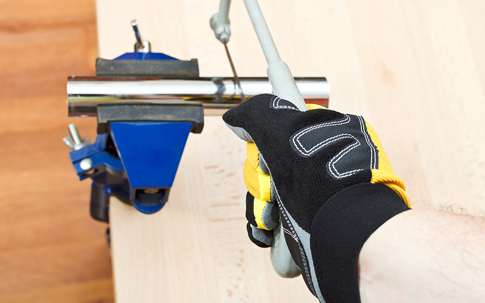 A person uses a hacksaw and vise to cut galvanized steel pipe.