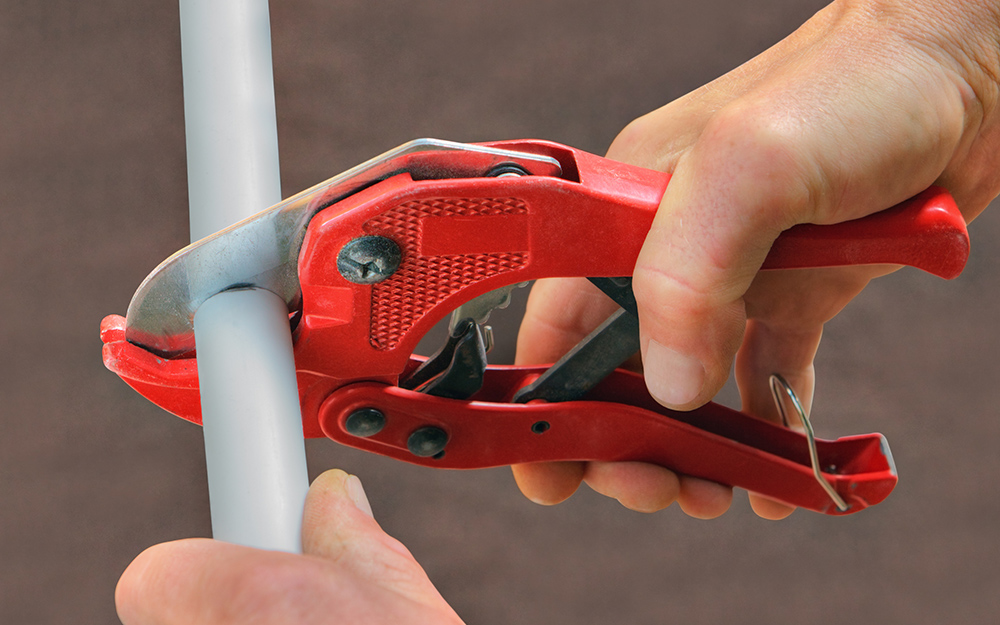 A person cuts pipe with scissor-type cutters.