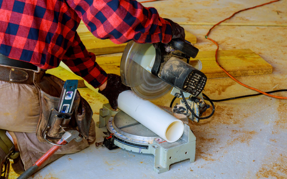 A person cuts pipe with miter saw.