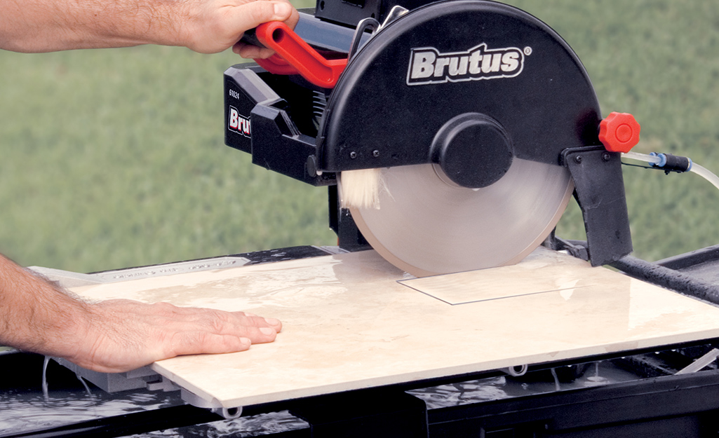 A person makes a plunge cut on a piece of tile with a wet saw.