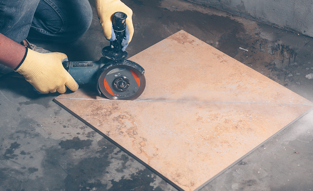 A person makes a diagonal cut on a piece of tile with a wet saw.