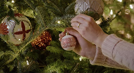 A woman hanging ornaments on a Christmas tree.