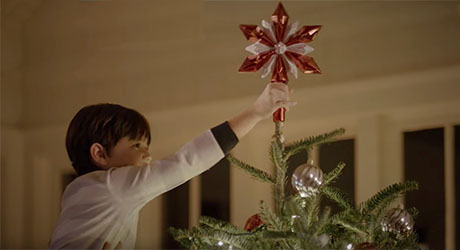 A child placing a star on top of a Christmas tree.