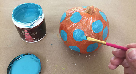 Painting a small whole pumpkin with decorative polka dots in bright blue.