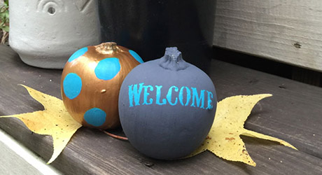 Pumpkin with wording stenciled on as decor.