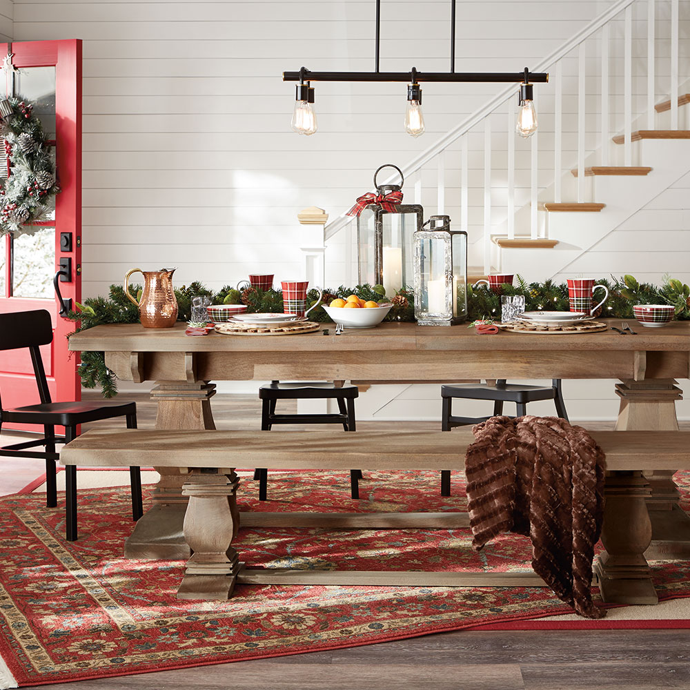 A dinner table is set in green and red decor for a holiday dinner.