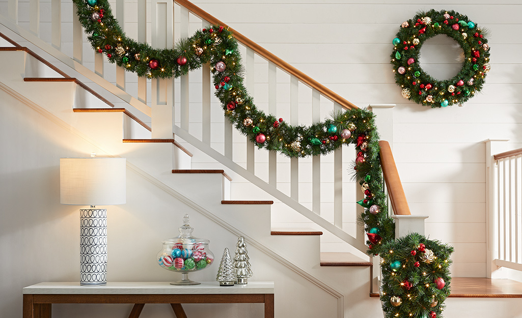 A stair well-wrapped with Christmas garland inside a home.