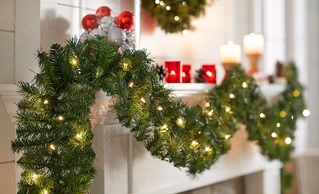 A mantel well-wrapped with Christmas garland inside a home.
