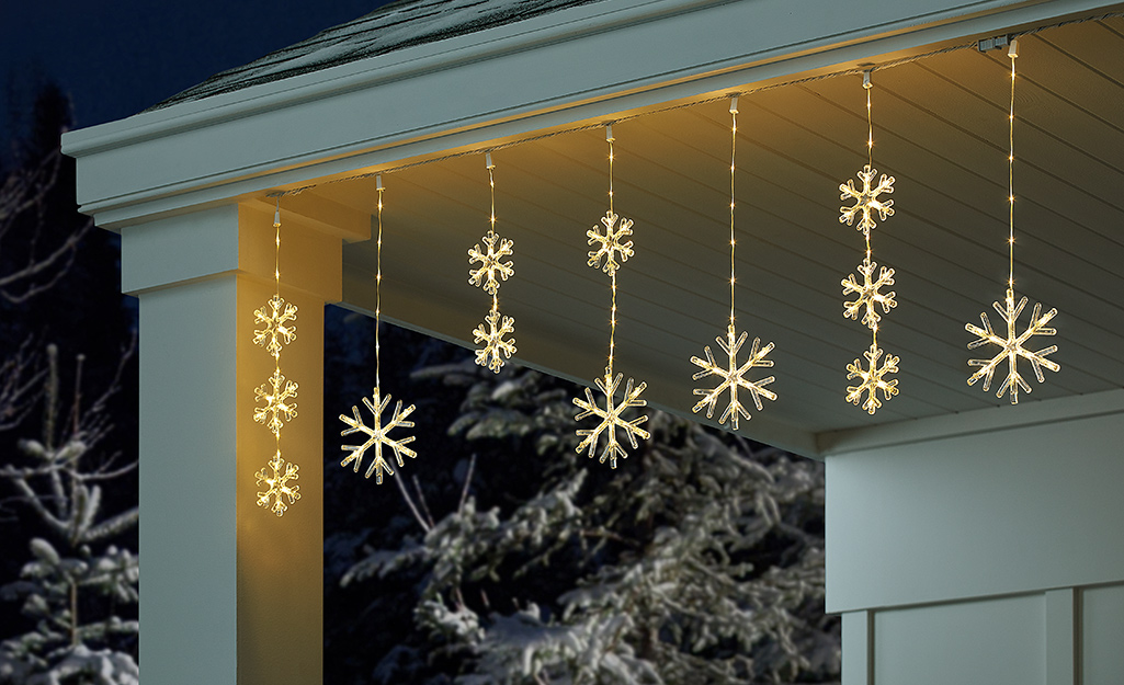 Snowflake Christmas lights hanging from the top of a home.