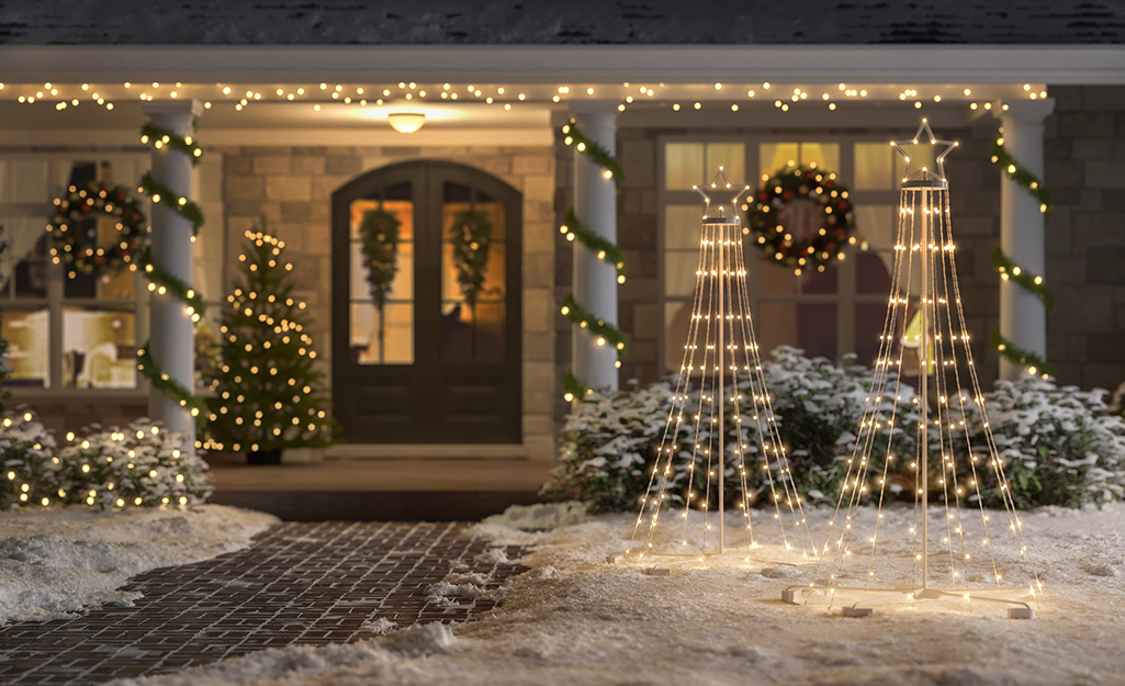 A front of a home well-lit with Christmas lights and decor.