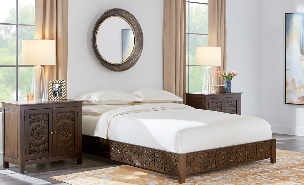 A bedroom with a bed, two night stands with lamps, an area rug and a large, round mirror over the bed.