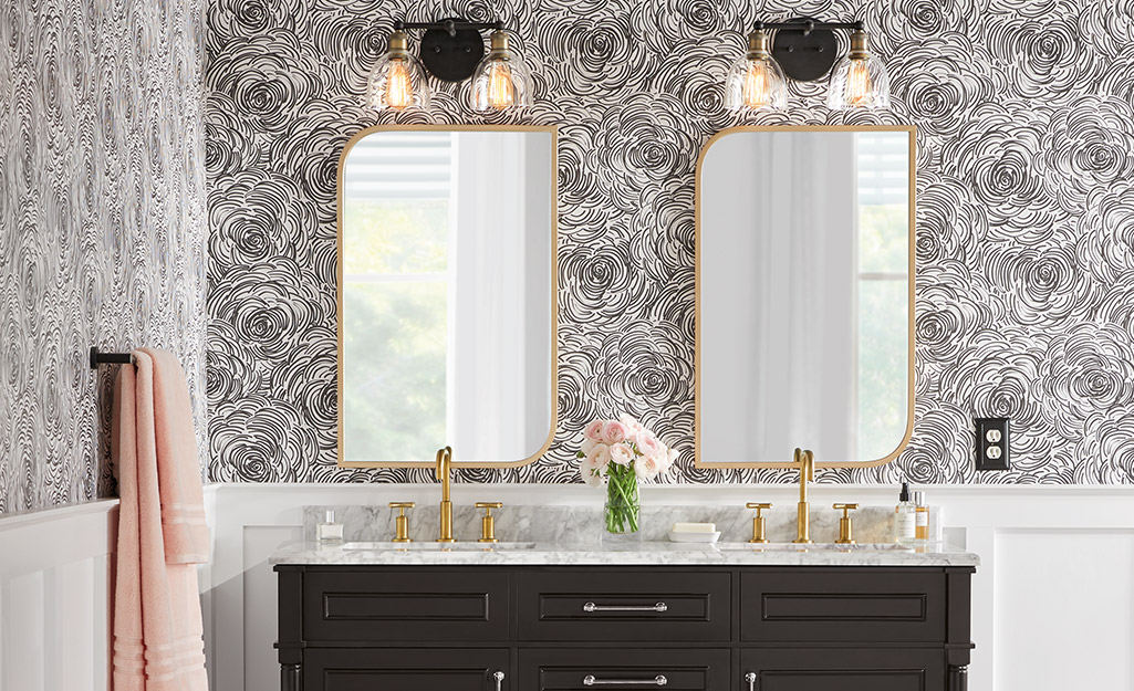 A bathroom with abstract wallpaper and matching mirrors with lamps hung over a dark vanity with gold finished faucets.