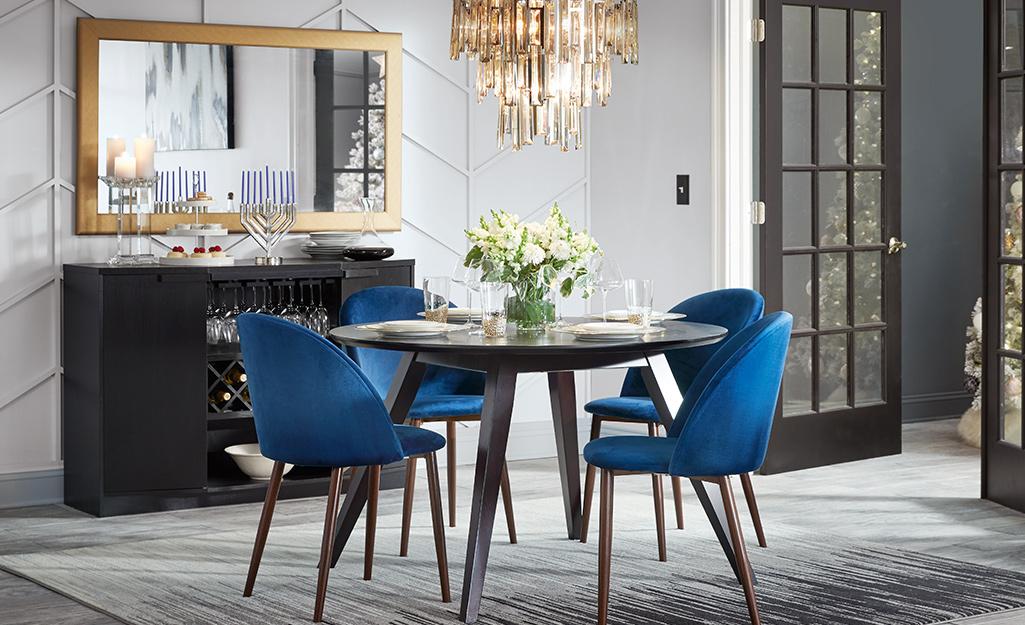 Một phòng ăn với một bàn và bốn ghế, một đèn chùm lớn và một chiếc gương hình chữ nhật viền vàng cho bữa tiệc tự chọn.