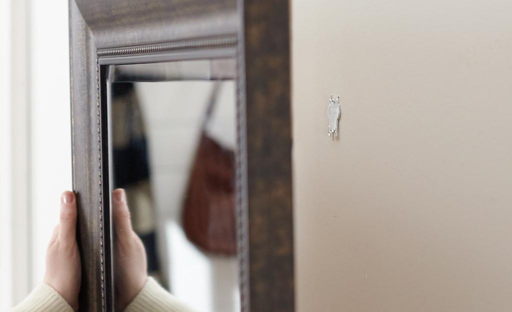 Ai đó đang treo gương trên tường bằng một cái móc.