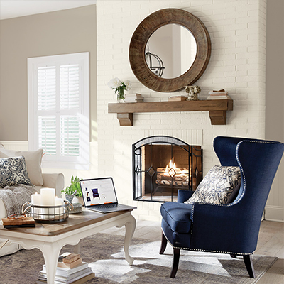 A living room with a blue wing chair, sofa, coffee table and large, round mirror over a fireplace mantle.
