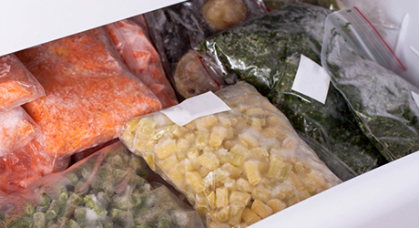 Packs of frozen vegetables in a freezer drawer.