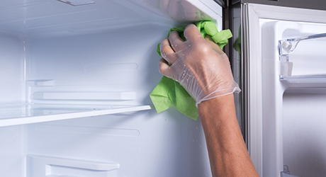 Person wiping the interior of a defrosted freezer.