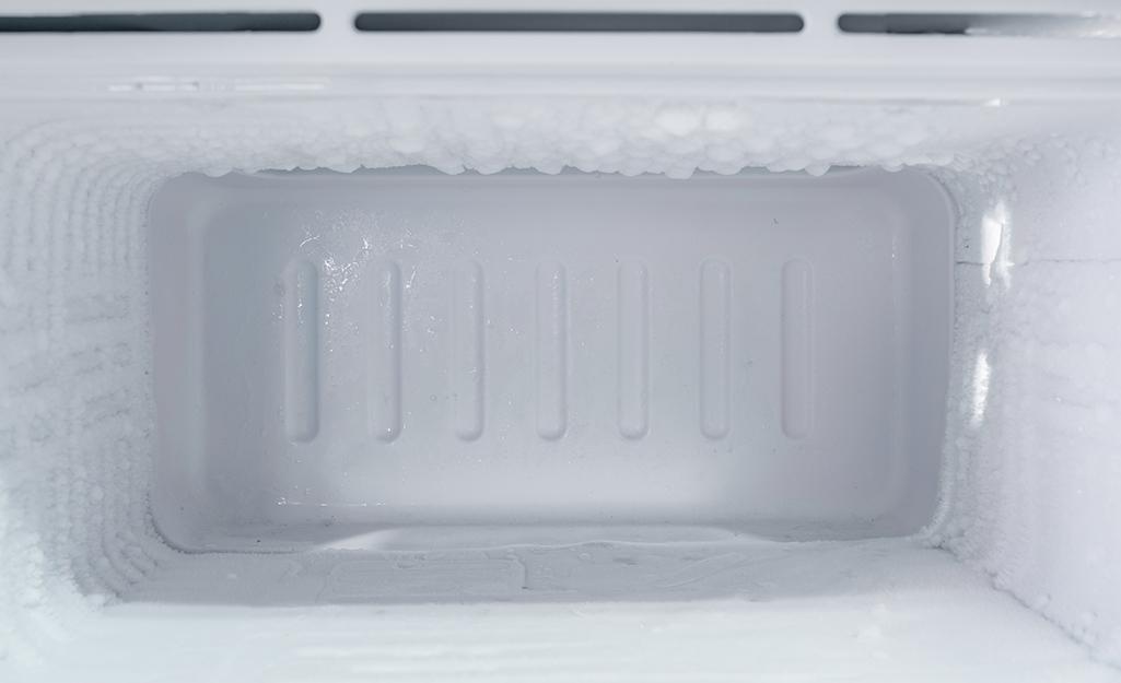Open freezer door revealing melting ice layer.