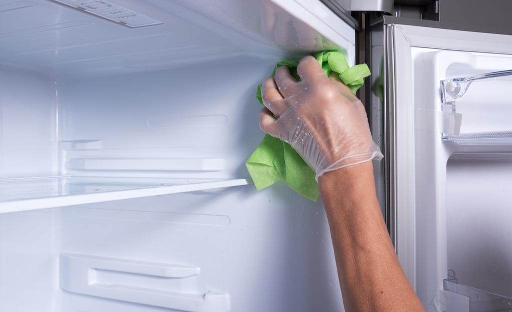 Person cleaning the inside of a fridge.