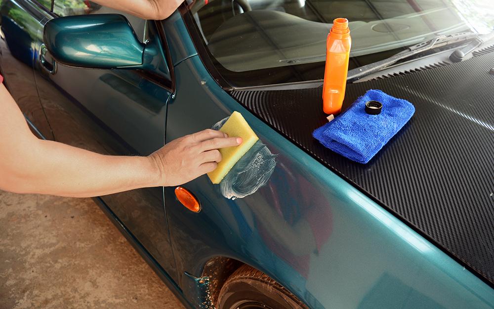 Một người tẩy lông bên ngoài xe hơi bằng miếng bôi.